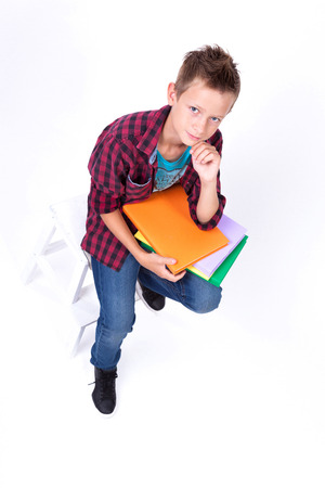tired schoolboy European appearance in shirt and jeans sitting on a chair with a book.  view from above Stock Photo