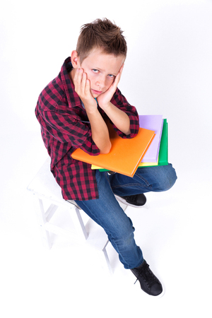 tired schoolboy European appearance in shirt and jeans sitting on a chair with a book. Photo from the depth of field
