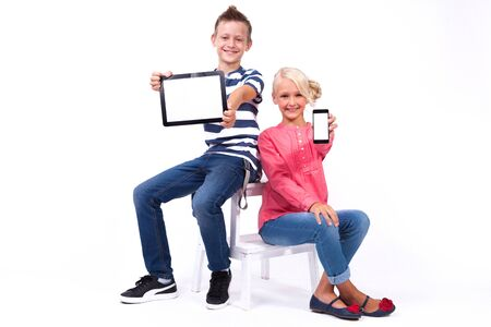smiling schoolchildren learn about the world and communicate with the help of modern tablets and phones, an interesting training and communication gadgets. Photo from the depth of field on a white background Stock Photo