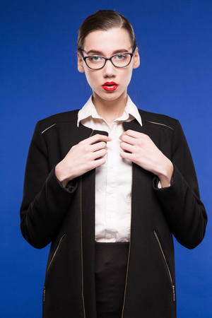 young girl in a black jacket and a white blouse on a blue background Stock Photo