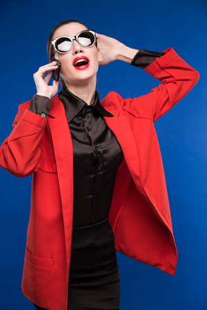 woman with red lipstick and a red jacket in the hands her phone