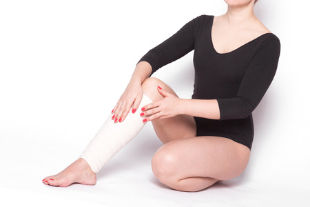 girl on a white background corrects an elastic bandage which tied her leg.