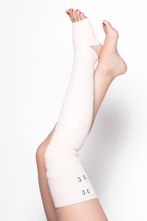ankle woman on a white background dragged elastic bandage. Stock Photo