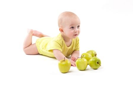 smiling baby lying on the background on among apples. Photo with depth of field Stock Photo