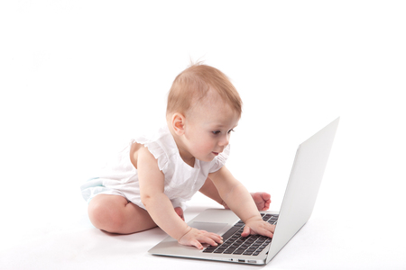 curious smiling child sitting near the laptop on a white background. Photo with depth of field