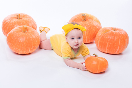 pretty baby girl in a yellow body with a yellow bow on her head lying on his stomach on a white background including pumpkins, picture with depth of field