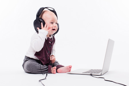 Cute baby sitting in front of a laptop wearing headphones on a white background smiling and listening to music, picture with depth of field Stock Photo