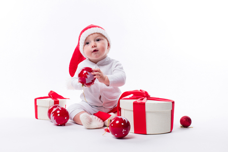 beautiful baby in the New Years cap and white body sits among boxes of holiday gifts and Christmas balls, picture with depth of field Stock Photo