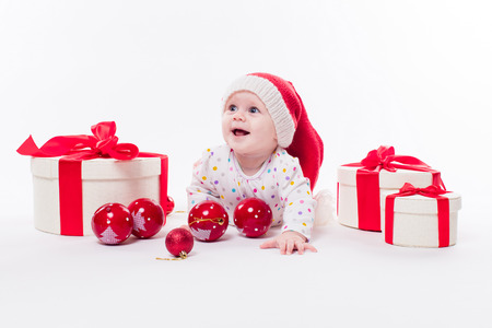 0ac626f5e3e Cute baby lying on his stomach in a New Years cap among Christmas balls and  red