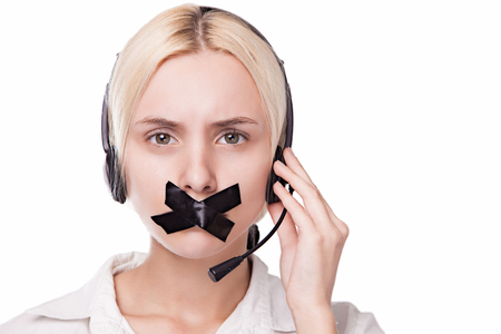 beautiful sexy blonde girl in headphones with a microphone on her head looking into the camera and can not speak because of the gummed tape mouth, picture with depth of field Stock Photo