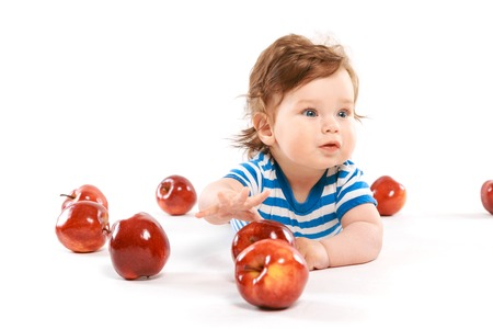 a newborn surrounded by apples on white background Stock Photo