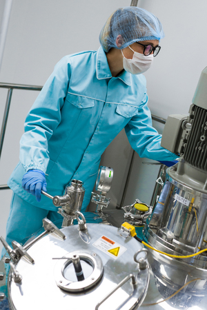 Scientists working with large vat in the lab Stock Photo