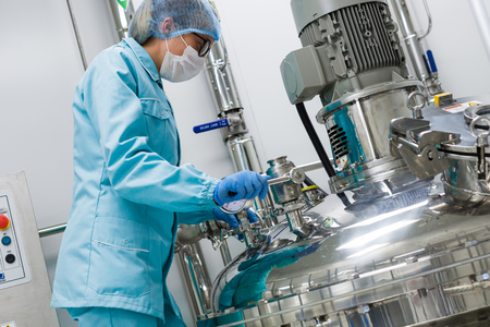 scientist woman in blue suit is checking pressure on tank