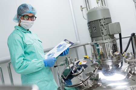 scientist in blue lab uniform stand near big pressure tank , hold tablet with graphs, look at camera