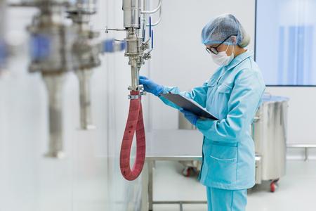 blured front, scientist in blue lab suit check readings of pressure meter, steel barresl on background, focus on scientist Stock Photo