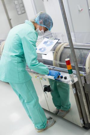 scientist checking control panel of machine Stock Photo