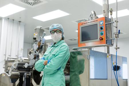 Ouvrier caucasien en costume de laboratoire bleu se tenir près du panneau de commande de l'ordinateur, machine sur fond, mains croisées Banque d'images - 89355113
