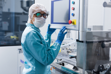 caucasian factory worker in blue lab suit configures machine, look at camera