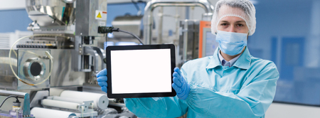 widescreen picture, blured background, caucasian scientist man in blue lab uniform stand near manufacture machine with shafts, show empty tablet, close picture, focus on tablet Фото со стока