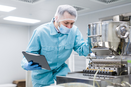 caucasian scientist man in blue lab suit work with big metal machine in clean room Banque d'images