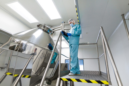 caucasian scientist in blue lab suit and gloves stand on steel ladder and make notes about chromed tank