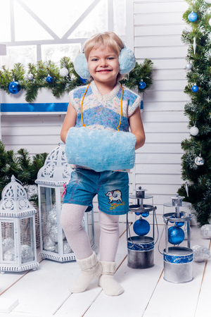 Smiling little pretty girl standing beside a Christmas tree and Christmas toys