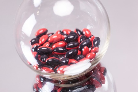 red-black capsule medical flask on the mirror background, macro, picture with depth of field Stock Photo