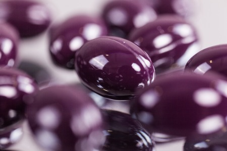 capsules purple pills on the mirror surface close up, macro, photos with depth of field