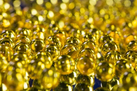 yellow medical capsules on a mirror surface picture with depth of field, macro