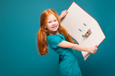 Isolated on blue, beautiful caucasian redhead child in azure dress, with long rusty hair, hold red paper folder, show folder to the camera