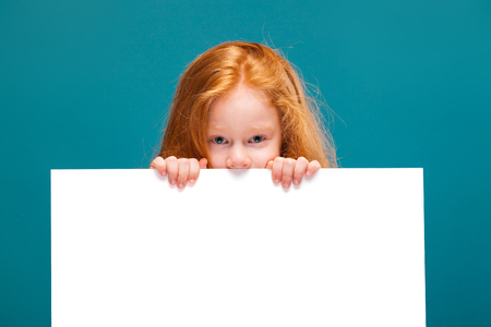 Isolated on blue, pretty, caucasian redhead child in blue striped dress, with long rusty hair show big empty poster, hide behind the poster