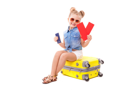 Isolated on white, little caucasian blonde girl in blue jeans shirt, white shorts, sunglasses and sandals sit on the yellow suitcase, hold red cards in hand and passport in other hand, look at camera