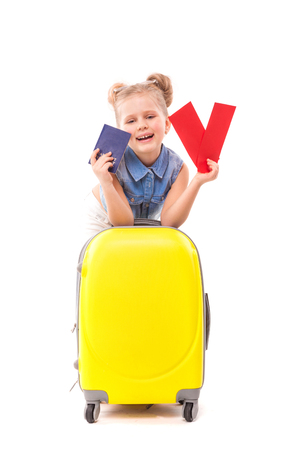 Isolated on white, little caucasian blonde girl in blue shirt, white shorts, sunglasses and sandals lean on the yellow suitcase, hold red cards in one hand and passport in other hand, laughing