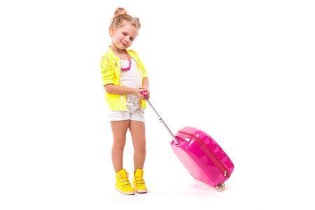 Isolated on white, cute little caucasian blonde girl in yellow shirt, white shorts, and yellow boots hold pink suitcase by the handle, look at camera, smiling, shy