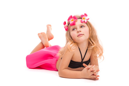 Isolated on white, pretty little caucasian blonde girl in pink skirt, black bikini and pink flower wreath, laying on belly, relies on hands, look up left Stock Photo
