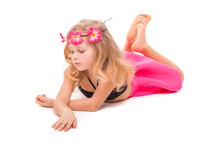 Isolated on white, pretty little caucasian blonde girl in pink skirt, black bikini and pink flower wreath, laying on belly, relies on hands, crossed hands