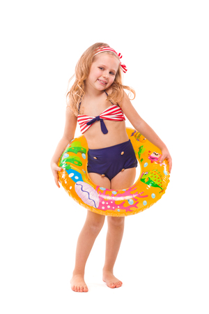 Isolated on white, pretty little caucasian blonde girl in red striped bikini, blue bottoms and pink flower wreath hold rubber ring on the waist, look at camera, hands on the ring Vertical picture