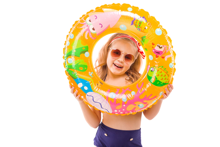 Isolated on white, pretty little caucasian blonde girl in red striped bikini, blue bottoms, sunglasses and pink flower wreath hold colorful rubber ring near her face, close