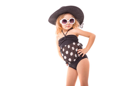 Isolated on white, beauty cute caucasian blonde girl in black swimwear, white sunglasses and big black hat stand, shy, hands on waist