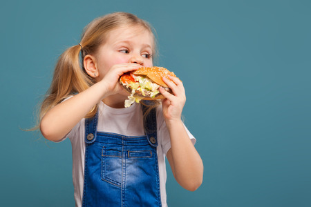 Isolated on blue, beautiful cute little caucasian blond girl in white shirt, white jacket, glasses and white shorts with hamburger, eats, look at right