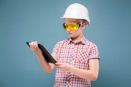 Confident young builder European appearance in the construction helmet and goggles holding a professional building tool in the hands, waist studio portrait on gray-blue background
