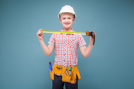 studio picture of a young confident teenager in helmet and protective glasses, holding a ruler, a belt hanging tools