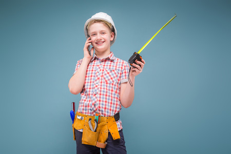 Young builder with construction tape measure in hand and protective helmet talking on a cell phone