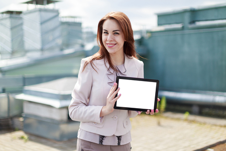 Blured roof on background, pretty redhead caucasian businesslady in beige suit stand on the roof and hold empty tablet, look at camera