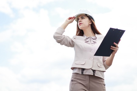 Blured sky on background, beauty redhead caucasian businesslady in beige suit, brown trousers and white helmet stand on the roof and hold tablet, crossed legs, look at far, hand on head