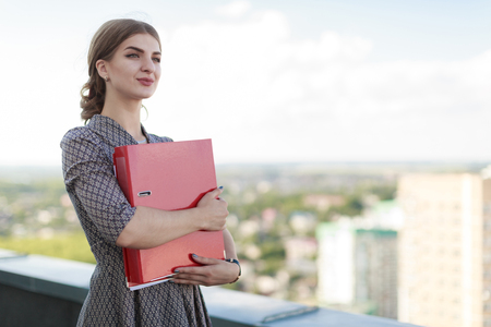Blured sky and sity on background, attractive brunette caucasian businesslady in patterned dress and watch stand on the roof and hold red paper folder, hugs folder