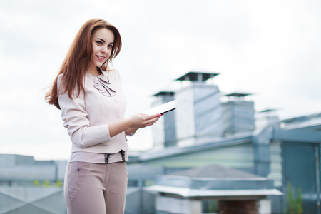 Blured roof on background, pretty redhead caucasian businesslady in beige suit stand on the roof and hold tablet