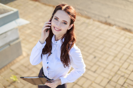Blured roof on background, attractive brunette caucasian businesslady in white blouse and black skirt stand on the roof and talk a phone, from top, look at camera Stock Photo