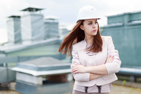 Blured sky on background, pretty redhead caucasian businesslady in beige suit and white helmet stand on the roof, crossed hands Stock Photo