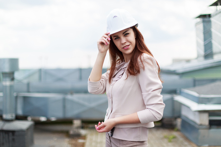 Blured sky on background, pretty redhead caucasian businesslady in beige suit and white helmet stand on the roof